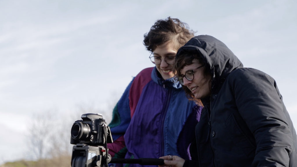 Zwei Personen mit Brille stehen zusammen hinter einer Kamera, auf die sie schauen. Foto: