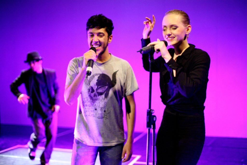 Das bild zeigt Ingrida Čepanonytė auf einer Bühne in ein Mirophon singen. Neben ihr steht eine zweite Person, die singt.
