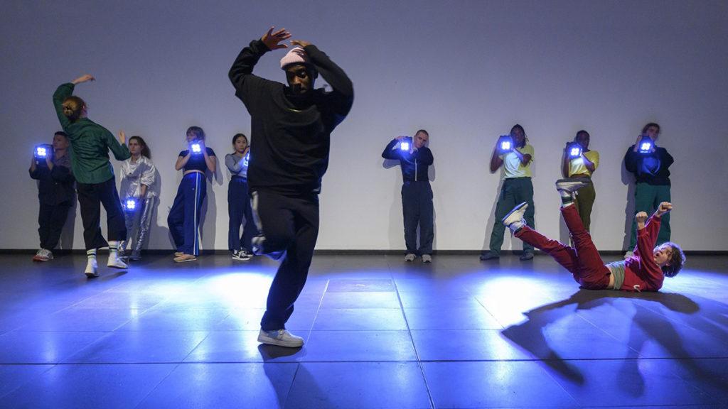 Drei Personen tanzen auf einer Bühne wöhrend im Hintergrund weitere Personen stehen und sie mit Strahlern anleuchten. Foto: Almut Elhardt