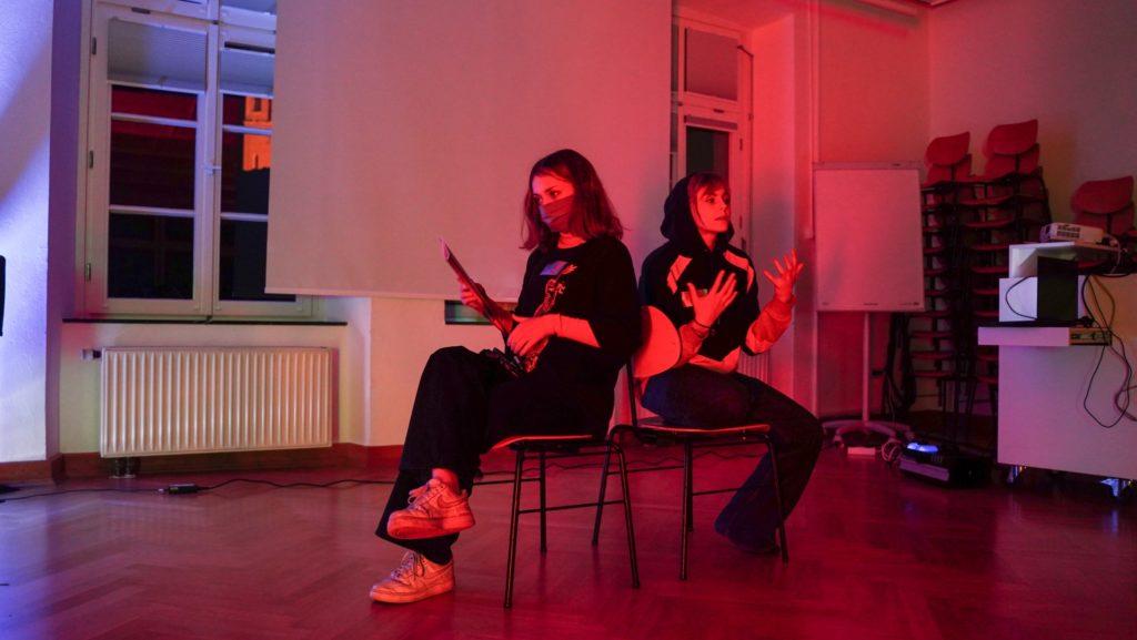 Zwei PErsonen sitzten in einem rot beleuchteten Raum auf zwei Stühlen nebeneinander. Foto © Yves Sanwidi