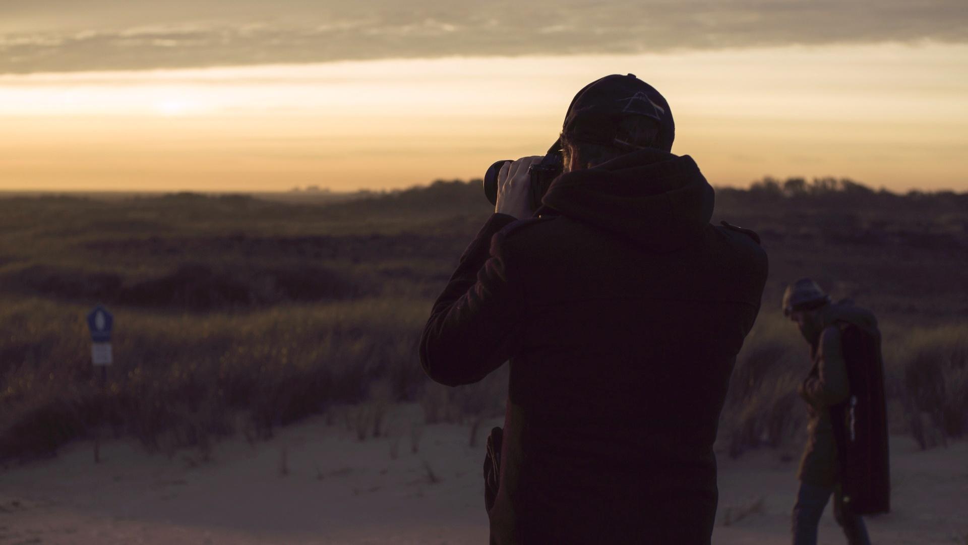 Person mit einer Kamera steht am Strand und macht Fotos von den Wiesen. Dahinter läuft einer weitere Person mit einer größeren Tasche auf einer Schulter. Foto: Gabriele Cinti