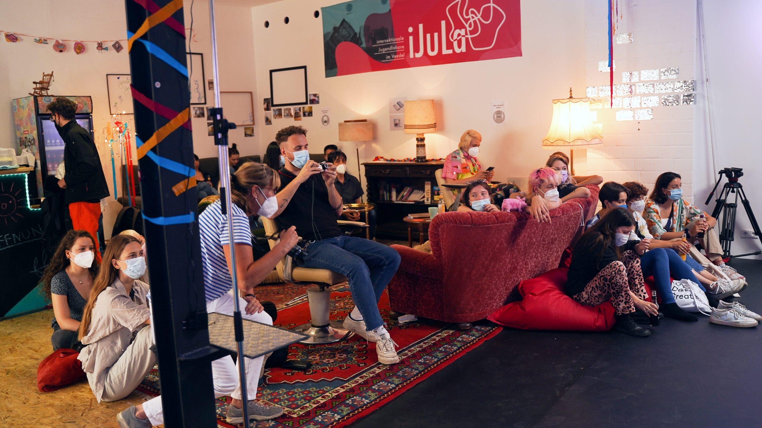 Menschen mit Mund-Nasenschützen sitzen in einem bequemen Raum mit Sofas