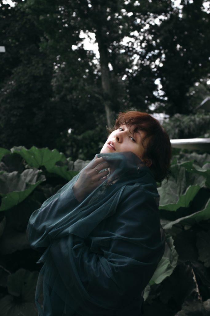Das Foto zeigt Anna Tafel. Sie Blickt in die Kamera - ihr Körper ist eingehüllt in ein grüne Tuch