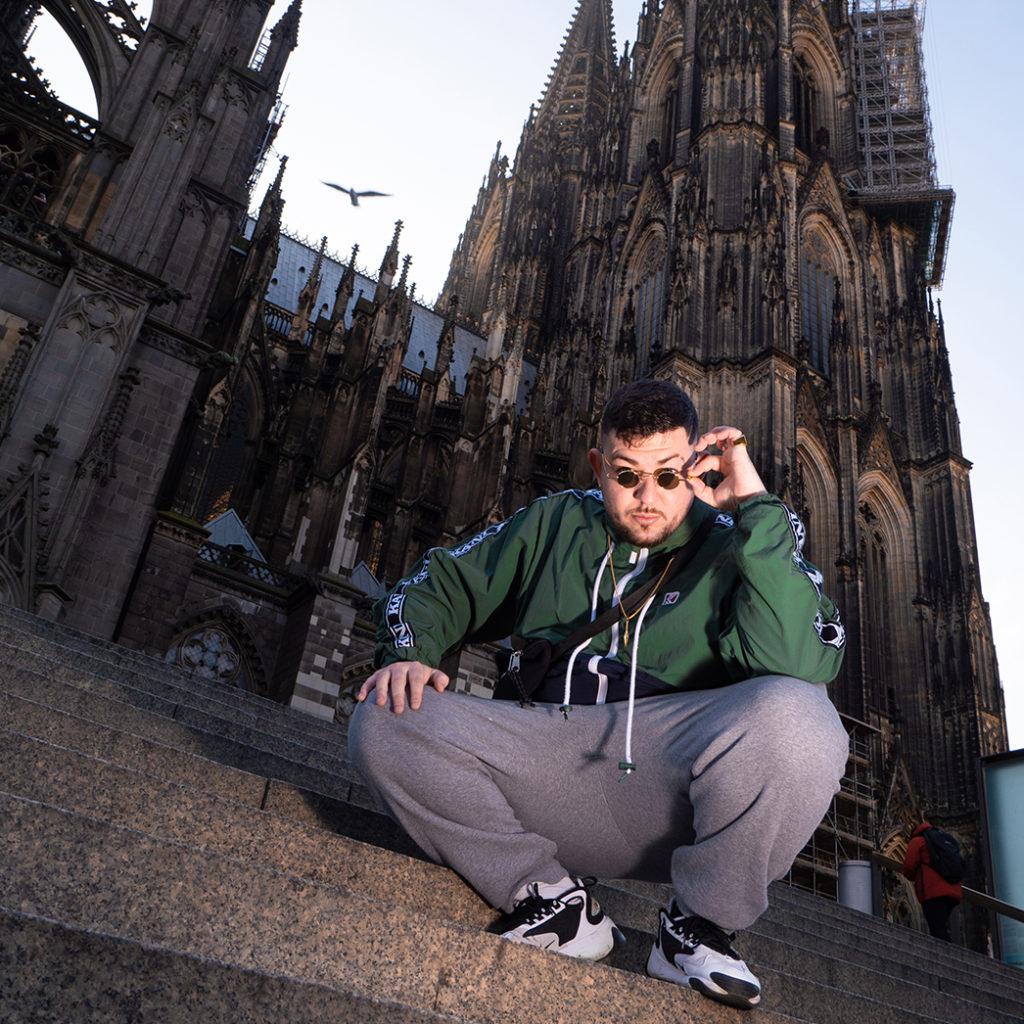 KABU sitz auf den Stufen vor dem Kölner Dom und schaut in die Kamara. Er hat eine Sonnenbrille auf und eine grüne Jacke an.