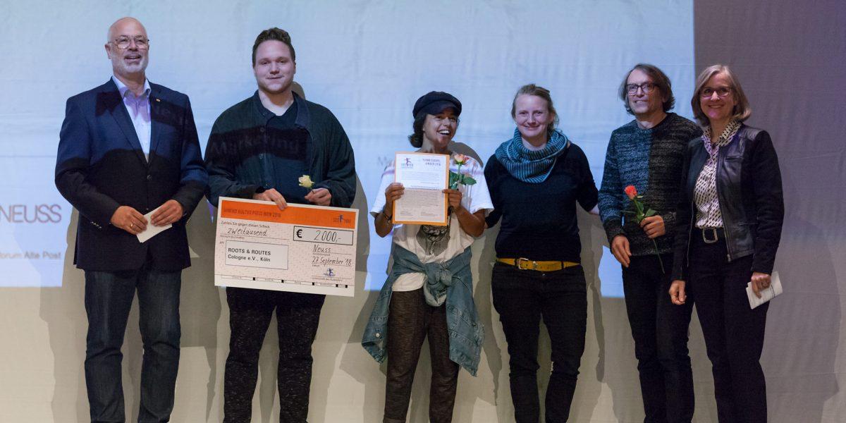 6 Personen stehen auf einer Bühne. Zwei Personen halten Zertifikate in die Höhe. Foto © Hanne Brandt