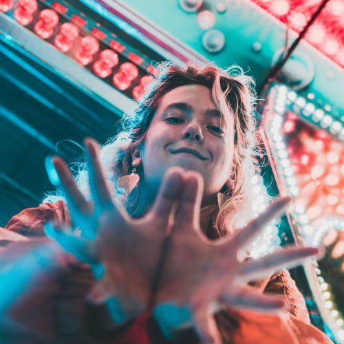 Eine Person schaut lächelnd auf die Kamera hinab und streckt ihre Hände danach aus. Die Person steht vor rot und blau leuchtenden lichtern. Foto © Francesca Pignanelli