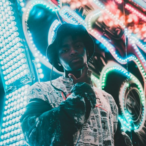 Eine Person mit Hut steht vor einer Bunt leuchtenden Lichterwand und fasst sich ans Kinn. Foto © Francesca Pignanelli