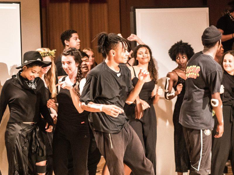Mehrere in schwarz gekleidete Personen stehen durcheinander, lachen und tanzen. Foto © Ignas Karlonas