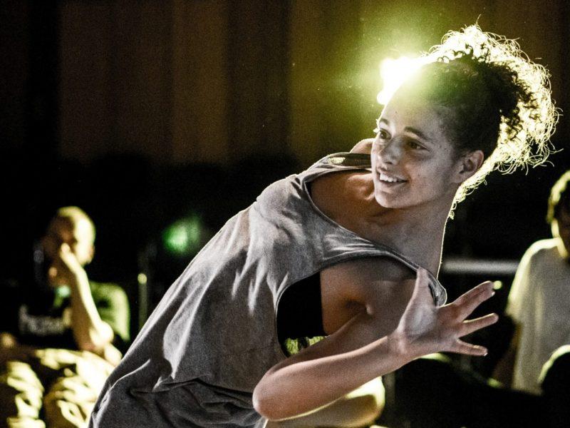 Eine Person tanzt und lächelt dabei. Weitere Personen sitzen im Hintergrund und schauen zu. Foto © Ignas Karlonas